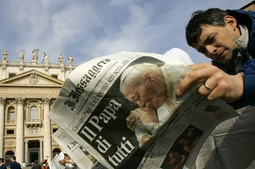 A faithful reads a newspaper before the start of a solemn mass for the death of the Pope in ...
