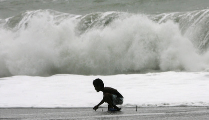 A boy plays near the heavy surf as Typhoon Lupit moves closer in Pagudpud, Ilocos Norte