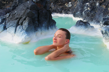 A woman enjoys spa in hot spring Blue Lagoon in Iceland