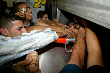 Palestinians cry near the body of Abu Samhadana after he was killed by Israeli air strike in Rafah
