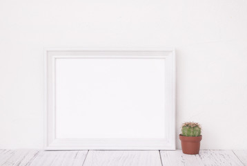 Stock photography of retro white frame template vintage wood table and cactus