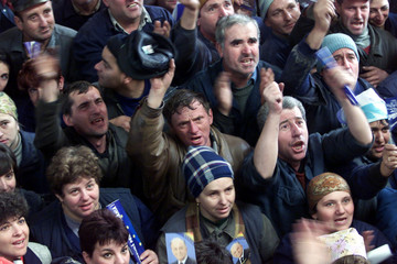 Industrial workers cheer leftist former President Ion Iliescu during an electoral rally at the Roman..