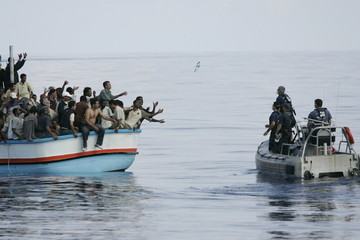 Armed Forces of Malta marines toss bottles of water to a group of illegal immigrants southwest of Malta