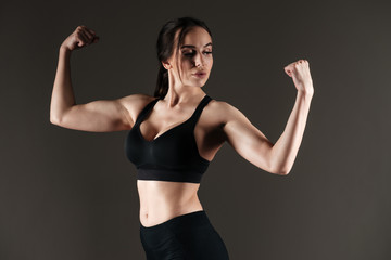 Serious strong sportswoman showing biceps
