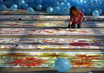 A child paints a flower on the world's longest painting ever made by children, in Bucharest