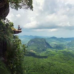 Woman sitin in lotus yoga pose at the cliff,province Krabi,Thailand