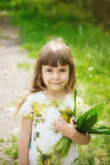 Girl with a bouquet of lilies of the valley. Selective focus.