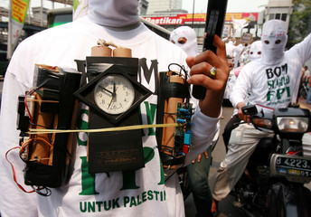 Protester from Islamic Defender Front wears mock bomb during rally against Israel's attacks in front of the U.N. office in Jakarta