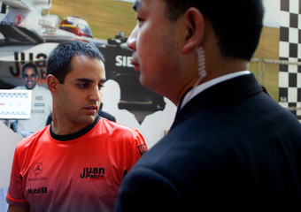 McLaren Formula One driver Juan Pablo Montoya of Colombia is escorted by a Chinese security personnel during a promotional event in Shanghai