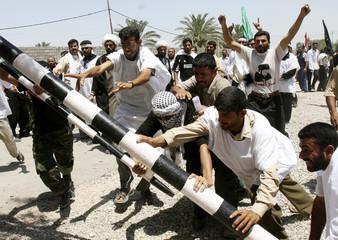 Iraqi demonstrators remove a barricade as they attack Iran's consulate in Basra
