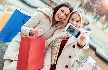 Shopping time. Beautiful smiling girls enjoying in shopping and taking a selfie with mobile phone. Consumerism, fashion, lifestyle concept