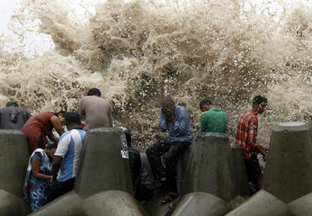 People get hit by waves from the Arabian Sea crashing on a seawall in Mumbai