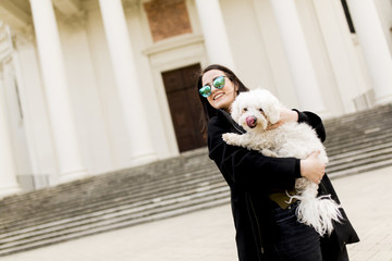 Beautiful happy young woman with cute small dog puppy have fun on street