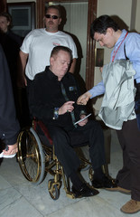 Larry Flynt, American pornography publishing head signs an autograph from his wheelchair as he arriv..