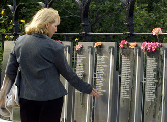 WOMAN TOUCHES THE NAME OF HER HUSBAND WHO WAS KILLED IN THE LINE OF DUTY AT MEMORIAL.