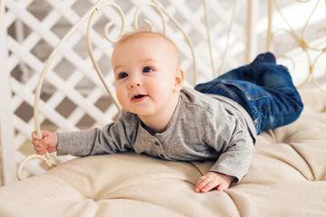 Adorable laughing baby boy in sunny bedroom. Newborn child relaxing. Family morning at home. Little kid lying on tummy