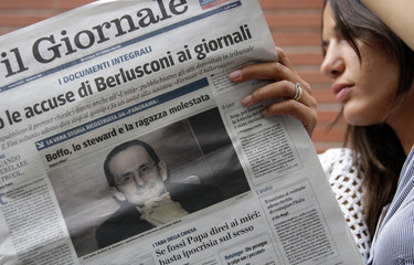 Two women read Il Giornale with picture Boffo, editor of Avvenire, on its front page in downtown Milan