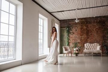 Beautiful brunette girl in dress posing in the interior, room, hotel