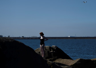 A woman enjoys the good weather at the Forty Foot diving area and beach in Sandycove