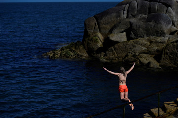 A woman jumps into the sea in the good weather at the Forty Foot diving area and beach in Sandycove