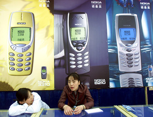 CHINESE SALESWOMEN WAIT FOR CUSTOMERS AT A MOBILE PHONE STORE IN BEIJING.