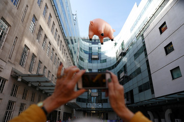 A woman photographs the Pink Floyd inflatable pig as it floats next to Broadcasting House to promote their new exhibition at the V&A museum, in London