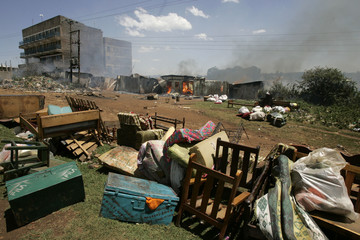 People's belongings lie on the ground as houses burn in the background in the town of Kericho