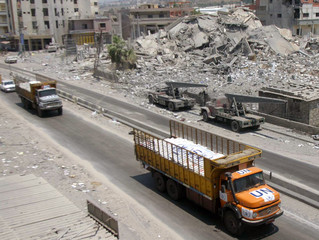 United Nations trucks loaded with aid of medical and food supplies drive past a damaged building in the village of Ghaziyeh in south Lebanon