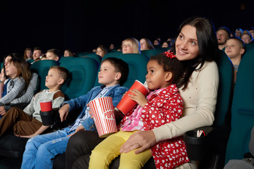 Cute little mulatto girl sipping her drink sitting on the lap of her mother at the cinema enjoying watching a cartoon copyspace family happiness positivity entertaining joyous childhood preschool.