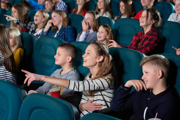 Shot of cheerful kids enjoying a movie at the cinema smiling pointing at the screen excitedly people childhood kids youth teenagers emotions expressive excitement entertainment leisure.