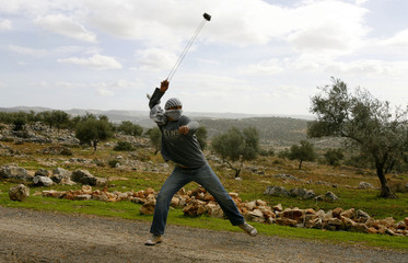 A Palestinian demonstrator uses a sling against Israeli troops during a protest near Israel's separation barrier in the West Bank village of Bilin