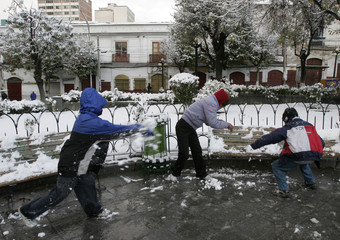 Bolivian children play with snow in the centre of La Paz