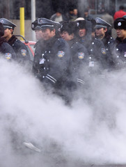 CHINESE SECURITY GUARDS MARCH THROUGH STEAM IN BEIJING.