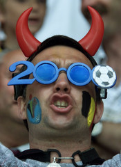 A Belgium fan with a painted face, plastic devil's horned helmet and Euro 2000 glasses sings before ..