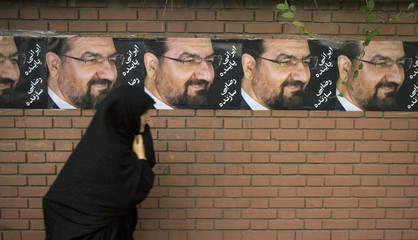 Woman walks past electoral posters for upcoming presidential election in Tehran