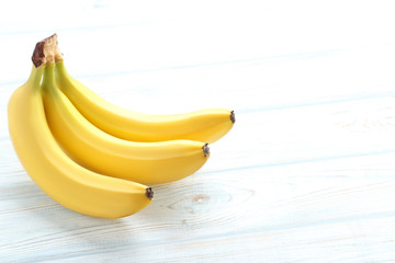 Sweet bananas on white wooden table