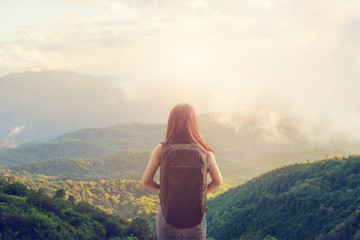 Tourist traveler concept, Young hipster girl with backpack enjoying sunset on peak mountain Wall mural