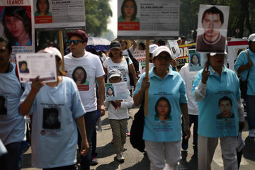Mothers and activists hold pictures of missing people during a march to demand justice for their missing relatives on Mother's Day in Mexico City
