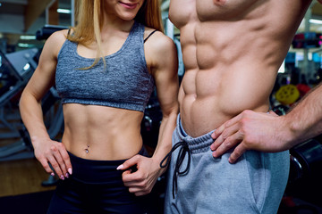 Beautiful sports body couple belly close-up in gym.