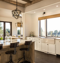 Beautiful Kitchen Detail in New Luxury Home at Sunrise. Features Cross Hatch Beams on Ceiling along with Beautiful Pendant Light Fixtures