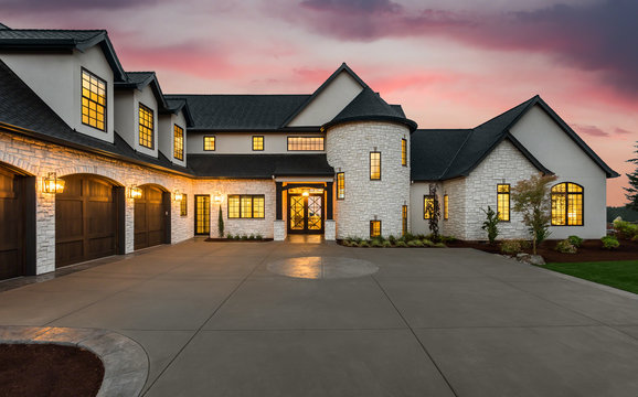 Stunning Luxury Home Exterior at Sunset with Colorful Sky and Expansive Driveway. This Mansion has Three Garages, Turret Style Tower, and Two Floors