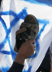 A protester holds up his shoe against an Israeli flag during a demonstration in Sanaa