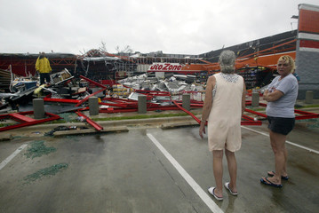 Women watch man cleans up auto parts store from Hurricane Charley in Florida.