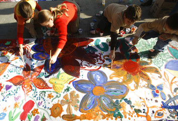 Children paint flowers on the world's longest painting ever made by children in Bucharest