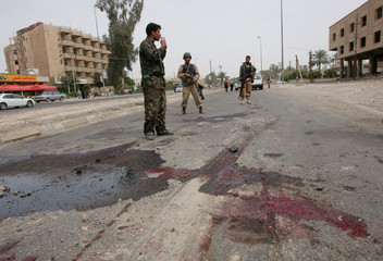 Iraqi soldiers secure the scene of a roadside bomb attack in Baghdad