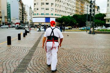 Man in a cook uniform walks down the street