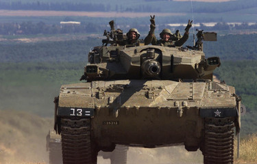 """Israeli members of a 'Merkava' tank both give the """"V"""" sign as their tank churns up dust on its way t.."""