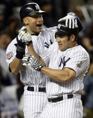 New York Yankees Jeter and Damon celebrate their each scoring a run in Game 6 of the 2009 Major League Baseball World Series in New York