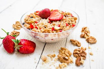 Oatmeal porridge with blueberries, strawberries, nuts and muesli on white wood background. Flat lay. Top view.
