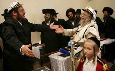 Ultra-Orthodox Jewish men dance while celebrating the Jewish holiday of Purim in a synagogue in the West Bank settlement of Modiin Illit